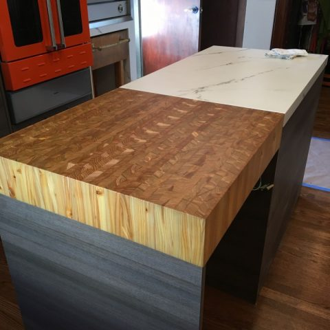 A custom made end grain kitchen chopping block integrated into a marble work surface.